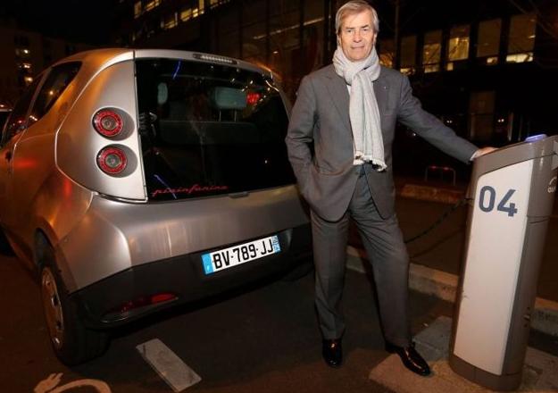 Photo de Vincent BOLLORE près des bornes électriques et de son véhicule électrique