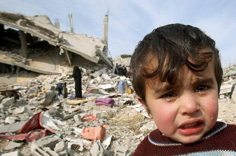 Un enfant pleure à GAZA devant des décombres